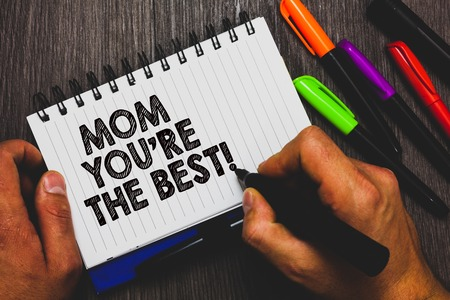 Word writing text Mom You re are The Best. Business concept for Appreciation for your mother love feelings compliment Hand holding pen and paper sketch words near lie some pen on woody desk