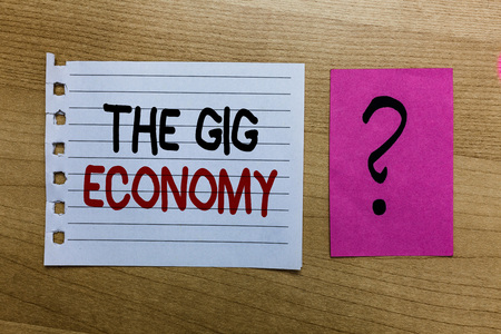 Conceptual hand writing showing The Gig Economy. Business photo text Market of Short-term contracts freelance work temporary white page on wooden desk with words violet with question mark