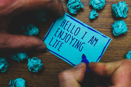 Writing note showing Hello I Am Enjoying Life. Business photo showcasing Happy relaxed lifestyle Enjoy simple things Foggy hand hold marker drawn blue notepad paper lump on wooden floor Imagens - 108713241