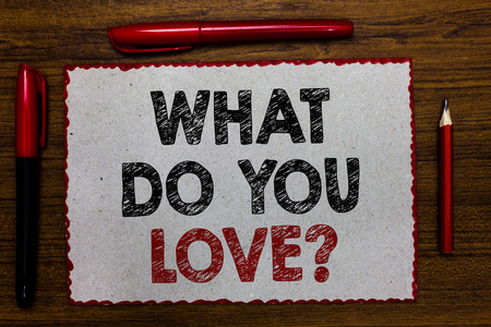 Text sign showing What Do You Love question. Conceptual photo Enjoyable things passion for something inspiration Red bordered white page centered some texts wooden desk pen pencil