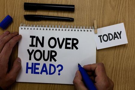 Word writing text In Over Your Head question. Business concept for To be involved in a difficult situation problem Hand hold pen notepad with words paperclip grip note paper woody base black pen