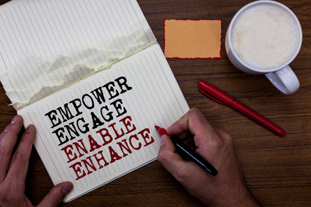 Handwriting text writing Empower Engage Enable Enhance. Concept meaning Empowerment Leadership Motivation Engagement Sticky note red pen coffee with coffee mug hand hold pen with written words