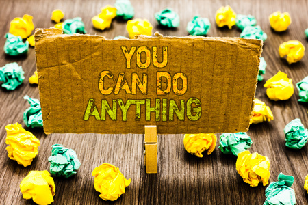 Text sign showing You Can Do Anything. Conceptual photo Motivation for doing something Believe in yourself Paperclip grip cardboard with texts many colorful lobs scattered on wooden desk Stock Photo