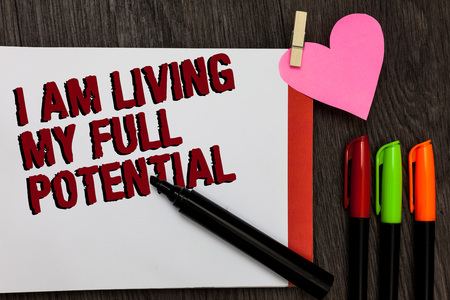 Writing note showing I Am Living My Full Potential. Business photo showcasing Embracing opportunities using skills abilities Bold red words pen on page small heart corner pens laid serially Stock Photo