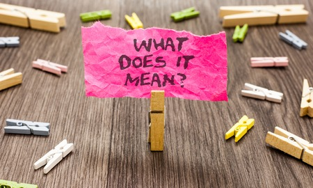 Conceptual hand writing showing What Does It Mean question. Business photo showcasing Give me the meaning of something Definition Paperclip hold pink note with texts many clips wooden floor