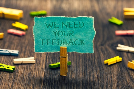 Conceptual hand writing showing We Need Your Feedback. Business photo showcasing Give us your review thoughts comments what to improve Paperclip retain blue cardboard blurry woody desk paper clip