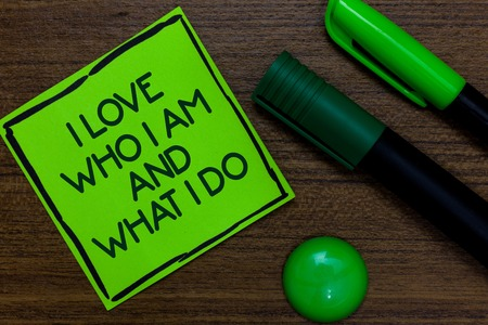 Text sign showing I Love Who I Am And What I Do. Conceptual photo High self-stem being comfortable with your job Written on sticky note two markers laid on wooden floor green ball Stock Photo