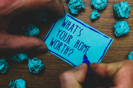 Writing note showing What s is Your Home Worth question. Business photo showcasing Value of a house Property Cost Price Rate Foggy hand hold marker drawn blue notepad paper lump on wooden floor