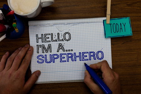 Conceptual hand writing showing Hello I am A ... Superhero. Business photo showcasing Special powers Cartoon character Customs strenght Hand hold pen paper clip written notepad pen case coffee mug Фото со стока
