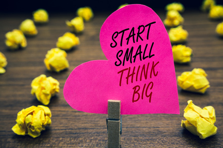 Conceptual hand writing showing Start Small Think Big. Business photo text Initiate with few things have something great in mind Paperclip hold pink written heart woody floor with yellow lobs