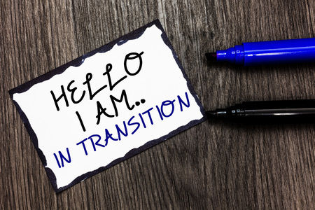 Word writing text Hello I Am.. In Transition. Business concept for Changing process Progressing planning new things Black bordered page with texts laid black and blue pen on wooden floor