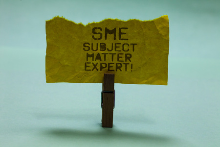 Text sign showing Sme Subject Matter Expert. Conceptual photo Authority in a particular area or topic Domain Paperclip hold torn yellow page written brown words sky blue background Imagens