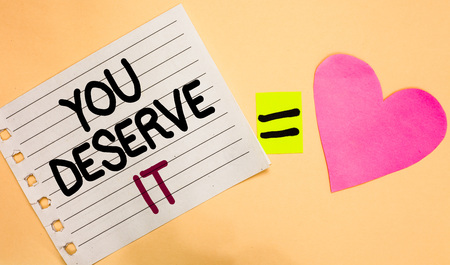 Text sign showing You Deserve It. Conceptual photo Reward for something well done Deserve Recognition award Transverse white paper with words equal love heart on Peach color base Stock Photo