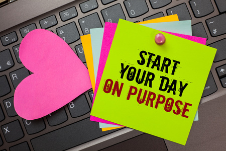 Text sign showing Start Your Day On Purpose. Conceptual photo Have clean ideas of what you are going to do Bright colorful written papers pinch by pin pink heart on computer keyboard Stock Photo
