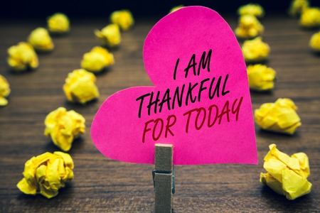 Conceptual hand writing showing I Am Thankful For Today. Business photo text Grateful about living one more day Philosophy Paperclip hold pink written heart woody floor with yellow lobs