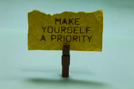 Text sign showing Make Yourself A Priority. Conceptual photo Think in your own good first personal development Paperclip hold torn yellow page written brown words sky blue background Stock Photo