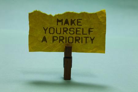Znak tekstowy pokazujący Zrób sobie priorytet. Zdjęcie koncepcyjne Pomyśl o swoim własnym dobrym pierwszym rozwoju osobistym Spinacz trzymaj rozdartą żółtą stronę napisaną brązowe słowa niebo niebieskie tło Zdjęcie Seryjne