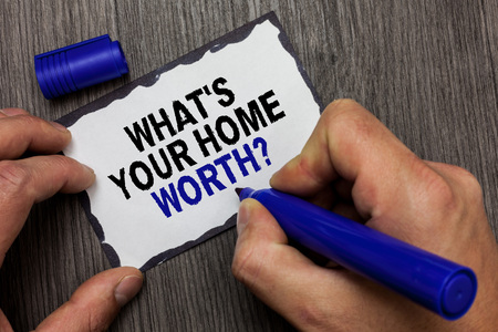 Handwriting text What s is Your Home Worth question. Concept meaning Value of a house Property Cost Price Rate Gray wooden deck hand hold black marker written black lined sticky note
