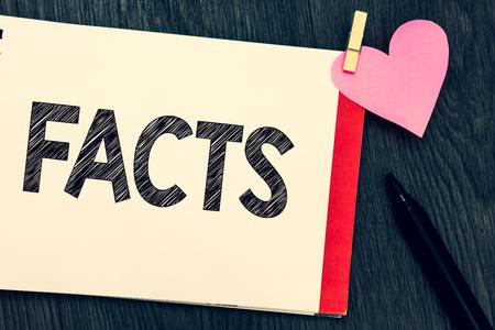 Schrijfbriefje met feiten. Zakelijke foto presentatie van informatie die wordt gebruikt als bewijs of onderdeel van rapport nieuwsartikel blog Notebook pagina marker wasknijper papier hart houten achtergrond te houden Stockfoto
