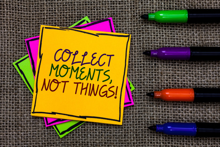 Text sign showing Collect Moments, Not Things. Conceptual photo Happiness philosophy enjoy simple life facts Written on some colorful sticky note 4 pens laid in rank on jute base