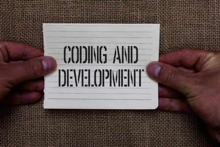 Text sign showing Coding And Development. Conceptual photo Programming Building simple assembly Programs Man holding piece notebook paper jute background Communicating ideas