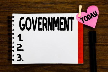 Conceptual hand writing showing Government. Business photo text Group of showing with authority to govern country state company Open notebook page markers holding paper heart wooden background Banco de Imagens