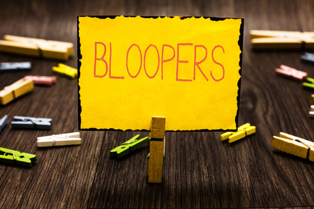Handwriting text Bloopers. Concept meaning Embarrassing errors Mistakes Fails Missteps Problems Failures Clothespin holding yellow paper note several clothespins wooden floor 스톡 콘텐츠