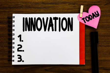 Conceptual hand writing showing Innovation. Business photo text New method idea product Different Creative Not known before Open notebook page markers holding paper heart wooden background