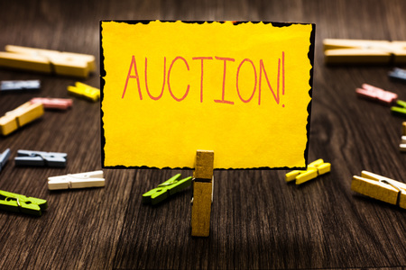 Handwriting text Auction. Concept meaning Public sale Goods or Property sold to highest bidder Purchase Clothespin holding yellow paper note several clothespins wooden floor