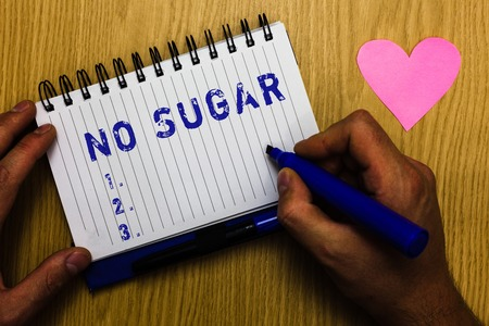 Text sign showing No Sugar. Conceptual photo has been left behind and replaced with artificial sweetener Man holding marker notebook page heart romantic messages wooden table