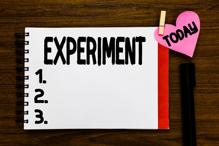 Conceptual hand writing showing Experiment. Business photo text Scientific procedure Make discovery test hypothesis demonstrate Open notebook page markers holding paper heart wooden background