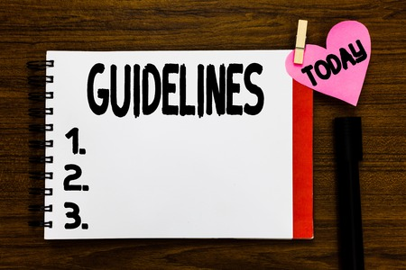 Conceptual hand writing showing Guidelines. Business photo text General rule principle piece of advice Policies Instructions Open notebook page markers holding paper heart wooden background 스톡 콘텐츠