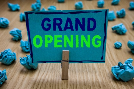 Handwriting text writing Grand Opening. Concept meaning Ribbon Cutting New Business First Official Day Launching Clothespin holding blue paper note crumpled papers several tries mistakes