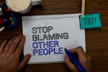 Conceptual hand writing showing Stop Blaming Other People. Business photo showcasing Do not make excuses assume your faults guilt Hand hold pen paper clip written notepad pen case coffee mug