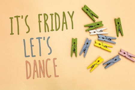 Text sign showing It s is Friday Let s is Dance. Conceptual photo Celebrate starting the weekend Go party Disco Music Yellow base with painted texts colorful paper clips laid randomly on ground