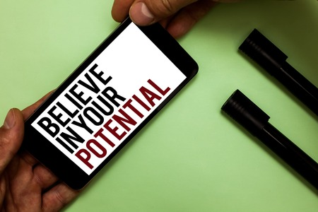 Text sign showing Believe In Your Potential. Conceptual photo Have self-confidence motiavate inspire yourself Mans hand hold iPhone with black and red words near two black marker