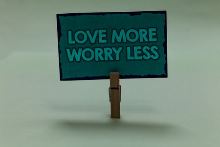 Writing note showing Love More Worry Less. Business photo showcasing Have a good attitude motivation be lovable enjoy life paperclip grip black lined green page with outlines grey background