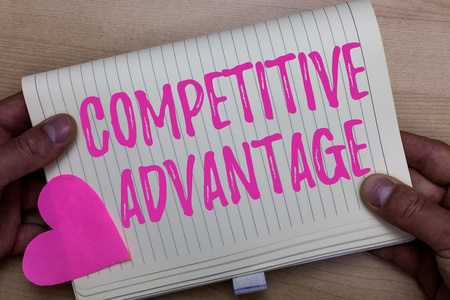 Writing note showing Competitive Advantage. Business photo showcasing Company Edge over another Favorable Business Position Man holding notebook paper heart Romantic ideas Wooden background 写真素材