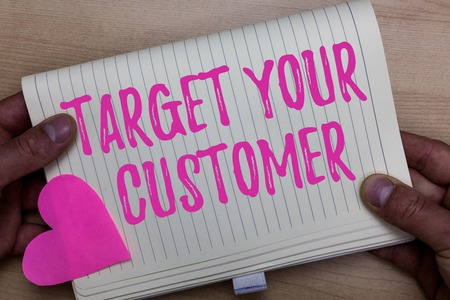 Writing note showing Target Your Customer. Business photo showcasing Tailor Marketing Pitch Defining Potential Consumers Man holding notebook paper heart Romantic ideas Wooden background