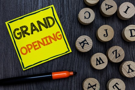 Conceptual hand writing showing Grand Opening. Business photo showcasing Ribbon Cutting New Business First Official Day Launching Yellow paper circle Marker express ideas wooden background Stock Photo