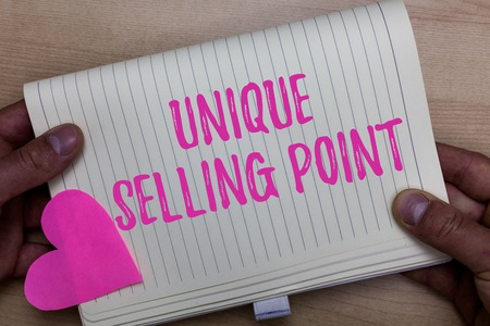 Writing note showing Unique Selling Point. Business photo showcasing Differentiate a Product Specific Features and Benefits Man holding notebook paper heart Romantic ideas Wooden background