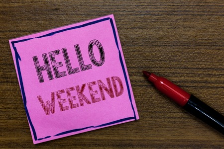 Text sign showing Hello Weekend. Conceptual photo Getaway Adventure Friday Positivity Relaxation Invitation Purple Paper Important reminder Communicate ideas Marker Wooden background