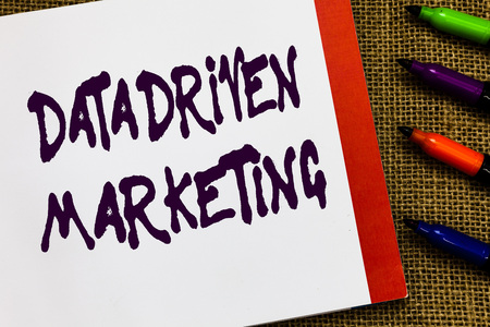 Handwriting text Data Driven Marketing. Concept meaning Strategy built on Insights Analysis from interactions Open notebook page jute background colorful markers Expressing ideas