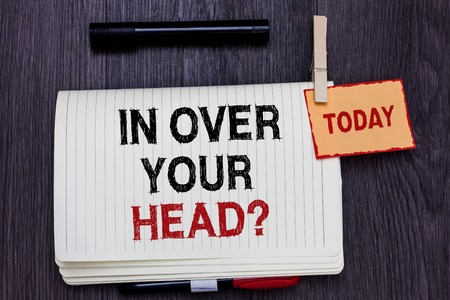 Handwriting text writing In Over Your Head question. Concept meaning To be involved in a difficult situation problem Written paper on wooden desk paper clip grip note with red words black pen