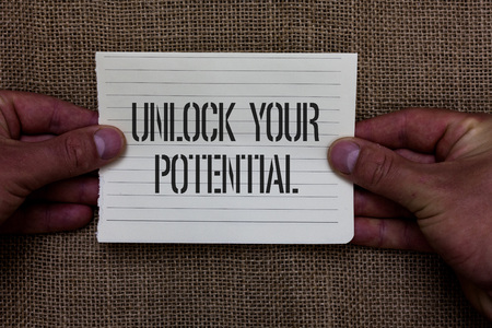 Text sign showing Unlock Your Potential question. Conceptual photo Maximize your Ability Use God given gift Man holding piece notebook paper jute background Communicating ideas Фото со стока