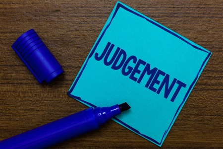 Writing note showing Judgement. Business photo showcasing ability make considered decisions come to sensible conclusions Blue Paper Important reminder Communicate ideas Wooden background Foto de archivo