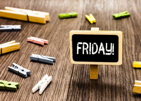 Handwriting text writing Friday. Concept meaning Last day of working week Start weekend Relax time Holiday leisure Blackboard standing several clothespins disorganized messy wooden floor