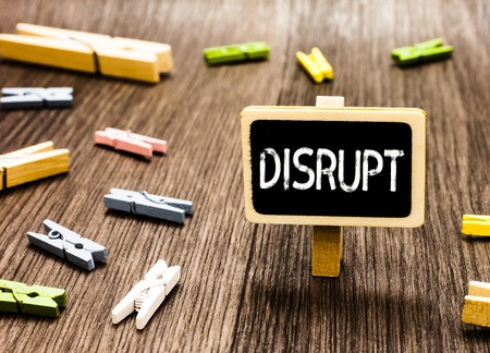 Handwriting text writing Disrupt. Concept meaning Interrupt causing disturbance problem Make something different Blackboard standing several clothespins disorganized messy wooden floor