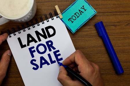 Writing note showing Land For Sale. Business photo showcasing Real Estate Lot Selling Developers Realtors Investment Man holding marker notebook clothespin reminder wooden table coffee Archivio Fotografico