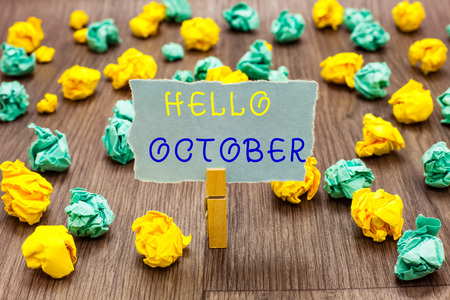 Text sign showing Hello October. Conceptual photo Last Quarter Tenth Month 30days Season Greeting Clothespin holding gray note paper crumpled papers several tries mistakes
